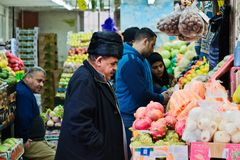 An elderly man chooses fruits and vegetables in the market in Je Royalty Free Stock Image