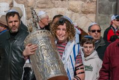 A 13 years old boy hold Torah scroll during celebrate Bar Mitzvah. JERUSALEM, ISRAEL - JANUARY 26, 2012: A 13 years old boy hold Torah scroll during celebrate royalty free stock image