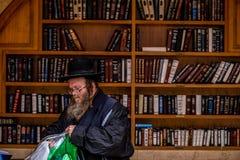 23/11/2016 Jerusalem, Israel, Juden sitzen nahe Regalen mit religiösen Büchern auf dem Quadrat lizenzfreies stockfoto