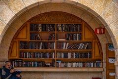 23/11/2016 Jerusalem, Israel, Juden sitzen nahe Regalen mit religiösen Büchern auf dem Quadrat stockbild