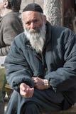 JERUSALEM, ISRAEL - 15. MÄRZ 2006: Purim-Karneval Porträt eines Vagabundbittens Ein älterer Mann in einer schwarzen Jacke, in ein Stockbilder
