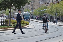 Jerusalem, Israel - 18. Mai 2018: Ein religiöser Jude kreuzt die Straße auf einer Straßenbahnbahn Verletzung von Verkehrsregeln,  stockbild