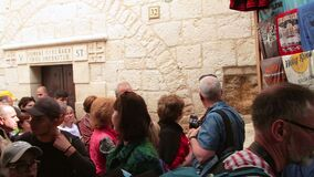 Christian tourists people visiting in the Jesus hand print in Via Dolorosa station 5 in the old city of Jerusalem