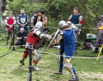 Two knights with shields and swords fight in the ring at the Purim festival with King Arthur in the city of Jerusalem, Israel royalty free stock images