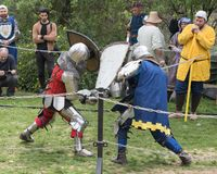 Two knights with shields and swords fight in the ring at the Purim festival with King Arthur in the city of Jerusalem, Israel royalty free stock photos