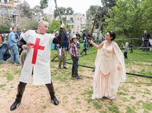 A visitor dressed in a crusader costume and a visitor dressed in costumes princesses fight with swords at the Purim festival with royalty free stock photo