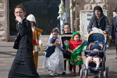 JERUSALEM ISRAEL - MARS 15, 2006: Purim karneval Ultra ortodox kvinna med barn som korsar vägen Arkivfoto