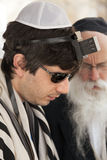 Tourist Wearing Phylacteries. Jerusalem, Israel - May 9th, 2012: An adult Caucasian man wearing a praying shawl, Yarmulke and Phylacteries, while being helped by Stock Image