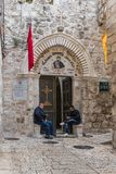 Believers sit near the entrance to St. Mark`s Church - The Syrian Orthodox Church in old city of Jerusalem, Israel. Jerusalem, Israel, November 24, 2018 stock photography