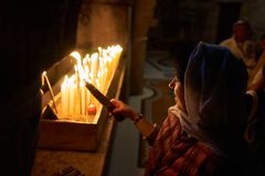 A woman is looking at a lighted bunch of 33 candles. By Jerusalem pilgrim`s Christian tradition a bunch of 33 candles shall be singed by the fire of the candles Stock Images