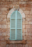 Jerusalem's ancient building's wall with blue aqua window shutters. retro filtered image Stock Photography