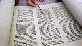 Jewish Rabbi read Torah scroll with TORA reading hand.