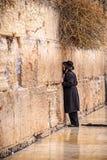 11/23/2018 Jeruzalem, Israël, die bidt Jood geloven dichtbij de muur van het schreeuwen in een grote zwarte hoed stock afbeeldingen