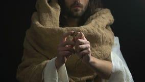Jesús en el traje que muestra la cruz cristiana, símbolo de la crucifixión, fondo oscuro almacen de video