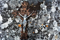 Jesús en la vieja y resistida cruz rota que miente en una piedra con el musgo negro Fotografía de archivo