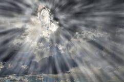 Jesús en nubes del cielo con los rayos de la luz Foto de archivo
