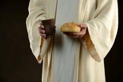Jesús que sostiene el pan y una taza de vino fotografía de archivo