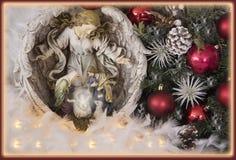 Jesús, Virgen María José y estatua del ángel adornada con la rama, los ornamentos, cornpine y el padre Imagenes de archivo