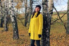 Jesień czas: piękna dziewczyna w żółtym żakiecie pozuje przeciw jesiennemu brzoza lasowi obrazy stock