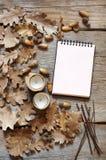 Jesień dąb opuszcza na starym drewnianym tle i notepad zdjęcie royalty free