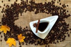Jesień domowy wystrój Kawowe fasole i rocznik biała ceramiczna filiżanka kawy, cynamonowi kije, anyż gwiazdy na jutowym worku kos zdjęcia stock
