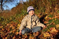 Jesień i chłopiec obsiadanie Obrazy Stock