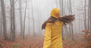 Jesień klimaty, mgłowa lasowa Atrakcyjna brunetki kobieta z długie włosy są ubranym żółtego strój i chodzą przez las zbiory