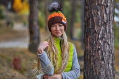 Jesień krajobraz, dziewczyna w kapeluszu, z długą blondyn pozycją z ona na brzeg jezioro z powrotem, Obrazy Stock