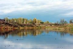 Jesień krajobraz Rzeka w którym chmurnieje i jest odbijający niebo Obrazy Stock