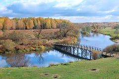Jesień krajobraz z rzecznym i drewnianym mostem Zdjęcie Royalty Free