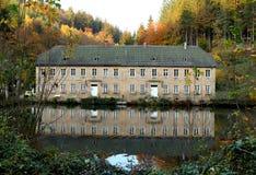 Jesień liście i budynek odbijali w wodzie obrazy stock