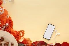 Jesień liście, smartphone i słuchawki na żółtym tle, obraz stock