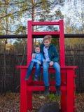 Jesień park, rozrywka Dwa dziecka siedzą na wielkim krześle zdjęcia royalty free