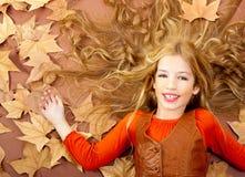 Jesień spadek mała blond dziewczyna na wysuszonych drzewnych liść Fotografia Royalty Free