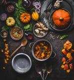 Jesień, zimy łasowanie z dyniowymi naczyniami i kucharstwo i Jarski gulasz w kucharstwo garnku z łyżki i warzyw składnikami dalej fotografia stock