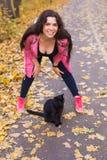 Jesień, zwierzęta domowe, ludzie pojęć - szczęśliwa kobieta śmia się z czarnym kotem obraz royalty free