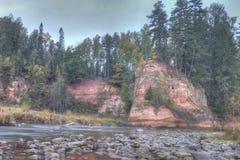 Jesień krajobraz i czerwieni kamienna faleza Amata rzeka, Latvia, Europa fotografia stock