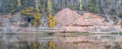 Jesień krajobraz i czerwieni kamienna faleza Gauja rzeka, Latvia, Europa zdjęcie stock