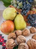 Jesieni żniwo winogrono orzechów włoskich jabłka na tradycyjnym ręczniku i bonkrety Fotografia Royalty Free