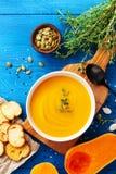 Jesieni bani kremowa polewka w pucharze słuzyć z ziarnami i crouton na drewnianym stołowym odgórnym widoku zdjęcie royalty free