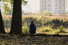 Jesieni chłopiec siedzi blisko jeziora obraz stock