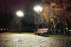 Jesieni dżdżysta noc z osamotnioną ławką pod spada jesień deszczem - nocy jesieni krajobraz Zdjęcia Royalty Free
