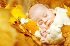 Jesieni dziecka nowonarodzony dosypianie w żółtych liściach Zdjęcia Royalty Free