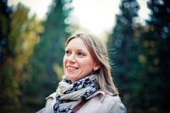 Jesieni kobieta szczęśliwa w spadku parku patrzeje wokoło mieć zabawę ono uśmiecha się w pięknym kolorowym lasowym ulistnieniu Zdjęcie Royalty Free