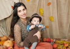 Jesieni kobieta z chłopiec na żółtych spadków liściach, jabłka, bania, dekoracja na tkaninie, szczęśliwa rodzina i kraju pojęcie, Fotografia Royalty Free