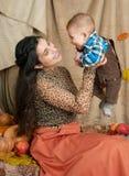 Jesieni kobieta z chłopiec na żółtych spadków liściach, jabłka, bania, dekoracja na tkaninie, szczęśliwa rodzina i kraju pojęcie, Zdjęcia Royalty Free