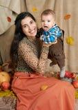 Jesieni kobieta z chłopiec na żółtych spadków liściach, jabłka, bania, dekoracja na tkaninie, szczęśliwa rodzina i kraju pojęcie, Obrazy Royalty Free