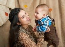 Jesieni kobieta z chłopiec na żółtych spadków liściach, jabłka, bania, dekoracja na tkaninie, szczęśliwa rodzina i kraju pojęcie, Fotografia Stock