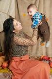 Jesieni kobieta z chłopiec na żółtych spadków liściach, jabłka, bania, dekoracja na tkaninie, szczęśliwa rodzina i kraju pojęcie, Obrazy Stock