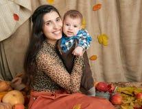 Jesieni kobieta z chłopiec na żółtych spadków liściach, jabłka, bania, dekoracja na tkaninie, szczęśliwa rodzina i kraju pojęcie, Zdjęcie Royalty Free